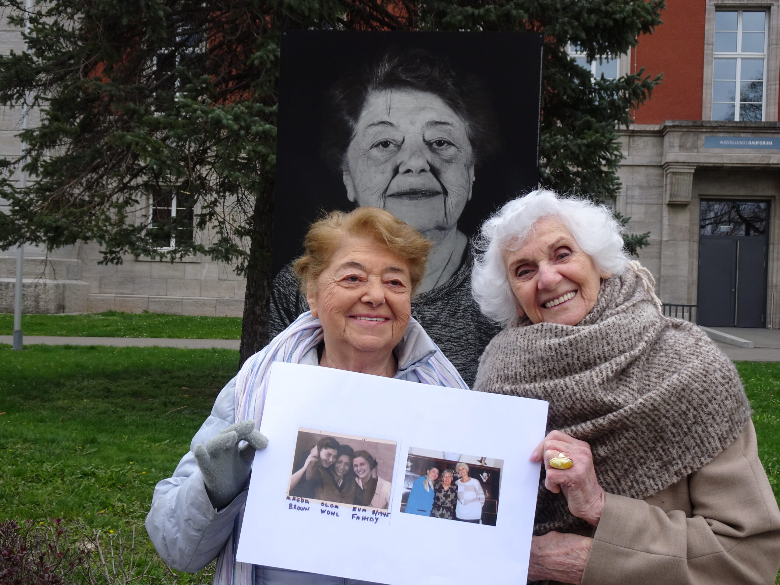 Magda Brown and Eva Fahidi Pusztai pose in front of Magda's portrait in Weimar holding photos of them from after the war and from the 1990s